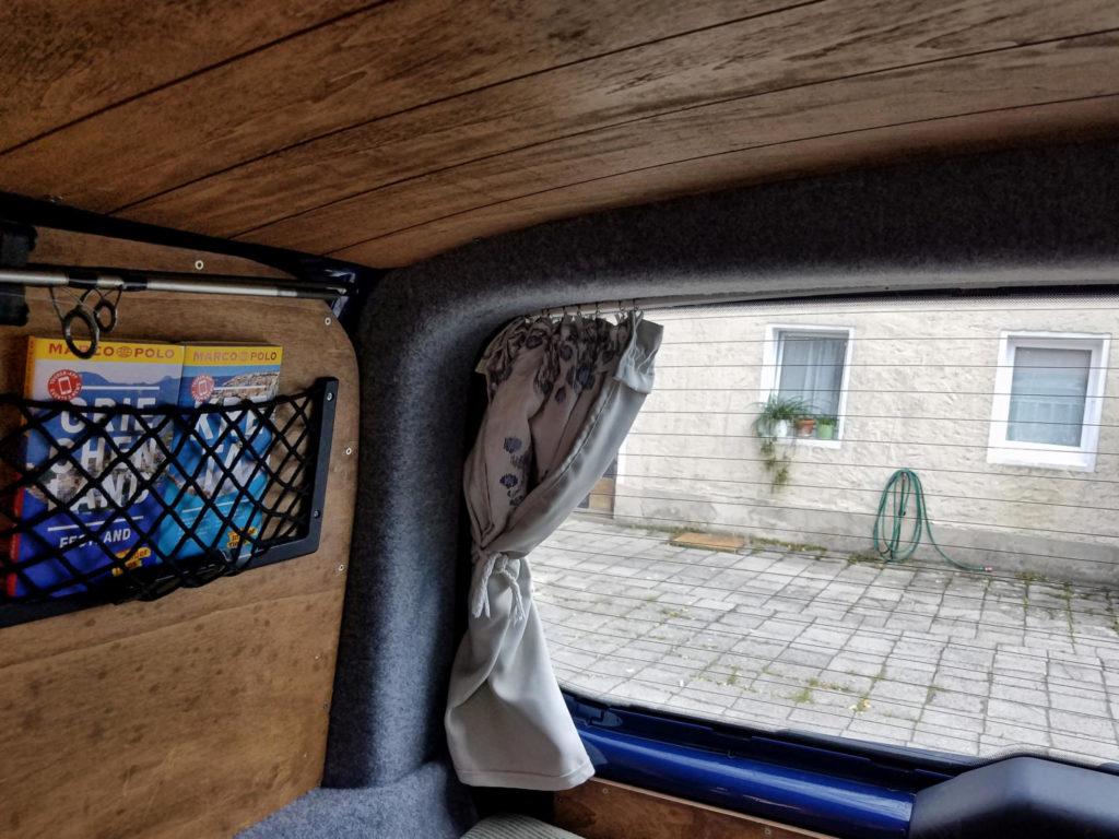 Die selbst genähten blickdichten Vorhänge im Camper an der eingebauten T-Schiene
